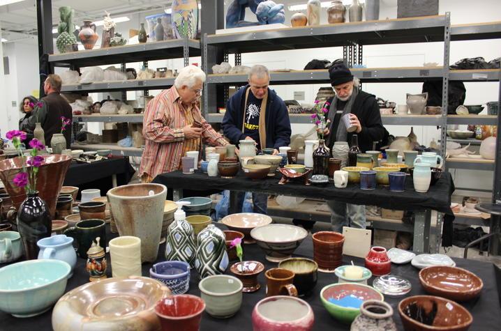 photo of people looking at ceramics in studio