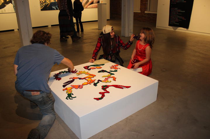 photo of child with 2 students looking at artwork at Open Studio 2017