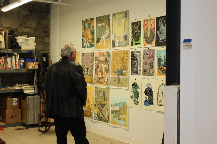 photo of man looking at art by UK student in his studio at Open Studio