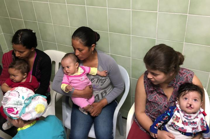 Photo of women with their children awaiting surgery screening