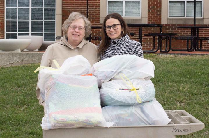 Chapter leader Rosemary Campbell presents 84 quilts and a number of other items to UK HealthCare's Lori Donelson.
