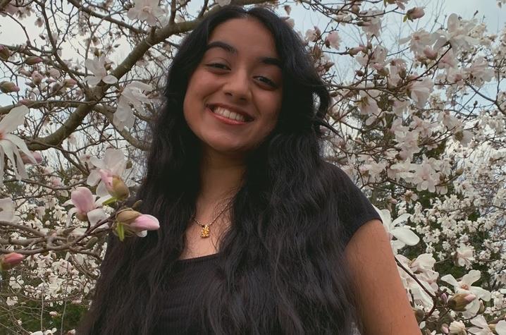 headshot photo of Isha Chauhan next to tree in bloom