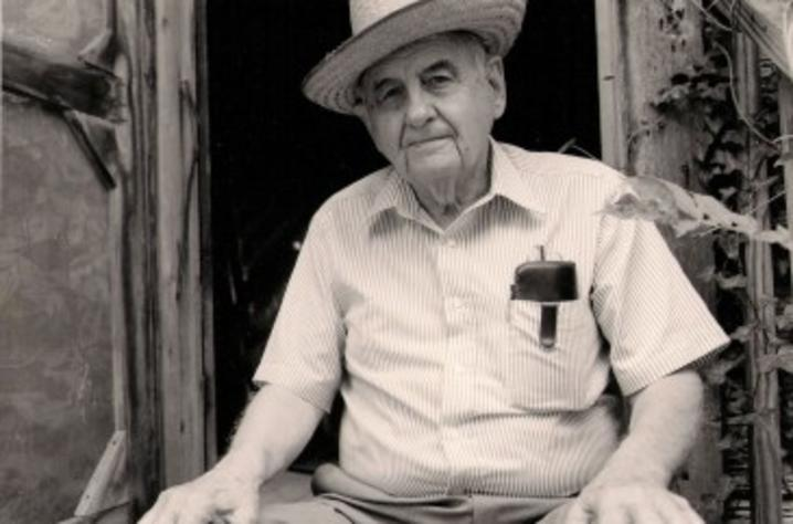 black and white photo of James Still seated with hat on, hand on his knees