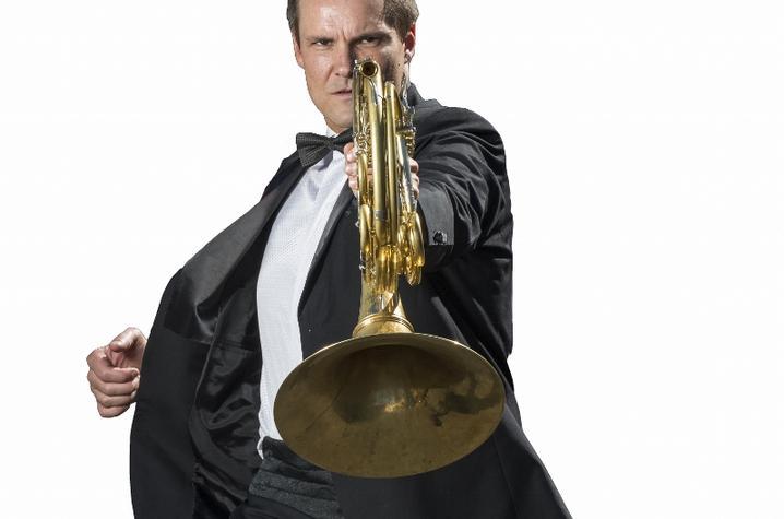 photo of Jeff Nelsen holding French horn in James Bond pose