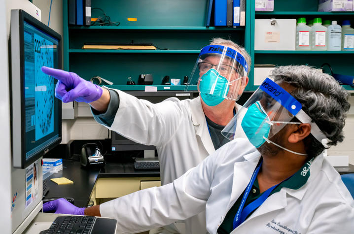 UK researchers Jerry Woodward and Siva Gandhapudi analyzing blood samples in FCIM's immune monitoring lab. Photo by Ben Corwin, Research Communications.