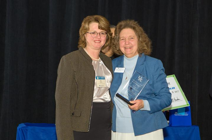 Kim Henken, left, presents award to Judy Hetterman