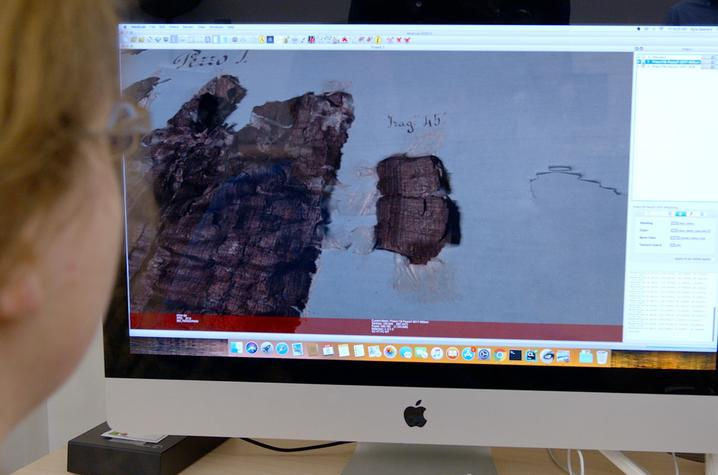 This is a photo of a masters student, studying digital images of a damaged manuscript.