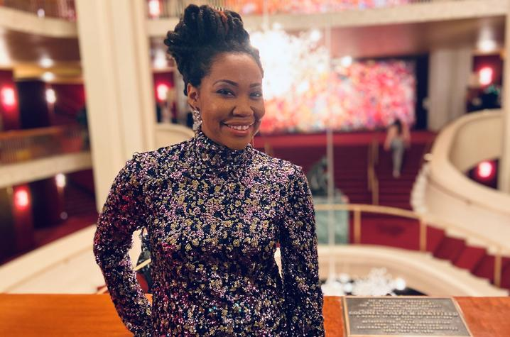 photo of Makeda Hampton inside the Met with a trademark chandelier behind her