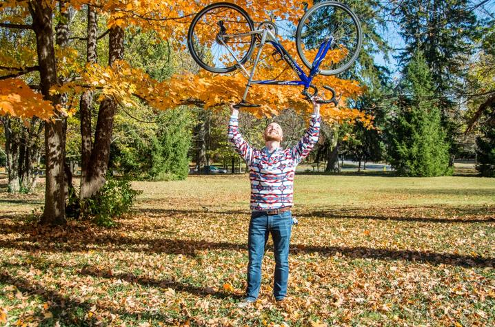 photo of Nate Williams holding bike over head with fall leaves - by Sally Horowitz Photography