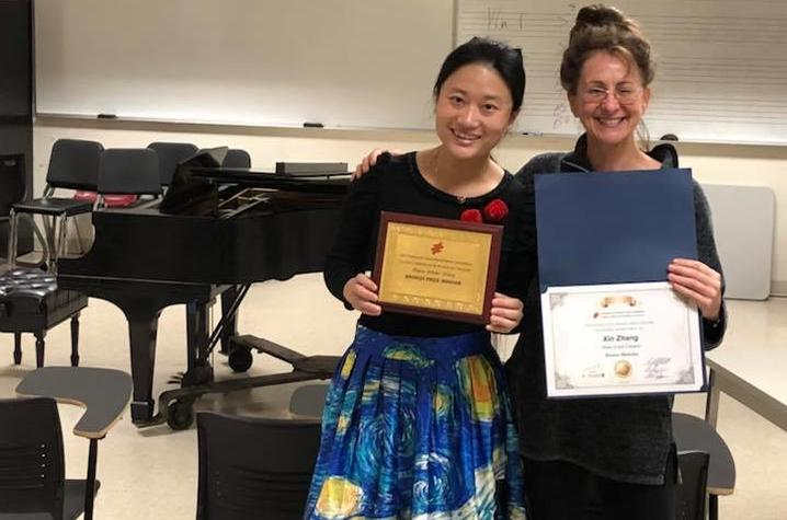photo of Olivia-Xin Zhang and Irina Voro with awards