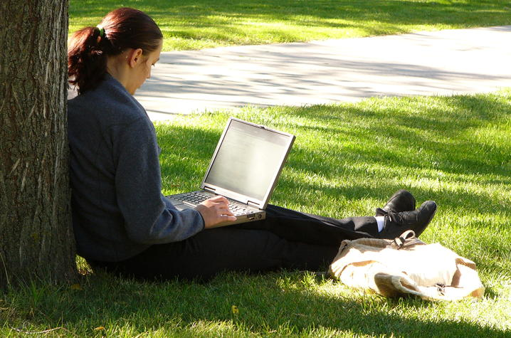 Woman leaning on a tree working on her computer.
