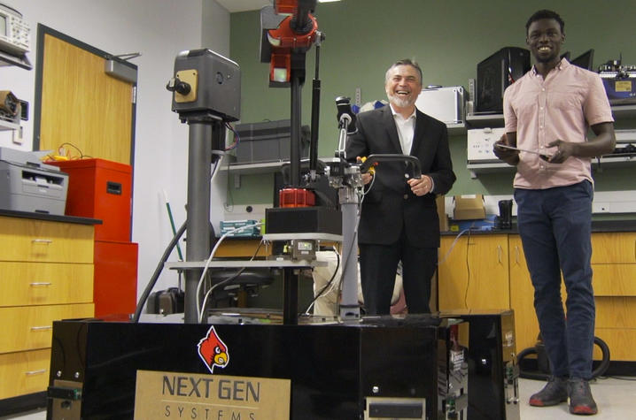 photo of Dan Popa with student, operating robot, at UofL