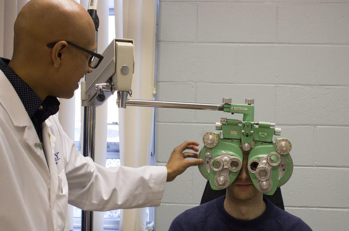 Paras Vora conducting an eye exam using a pale green phoropter