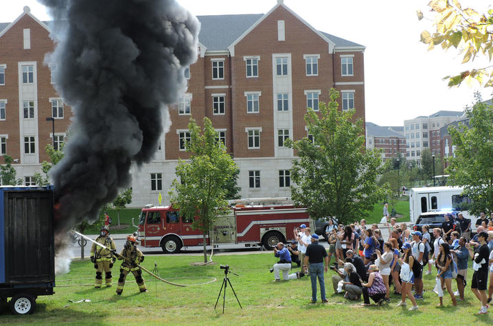 photo of burn demonstration near residence halls with student watching