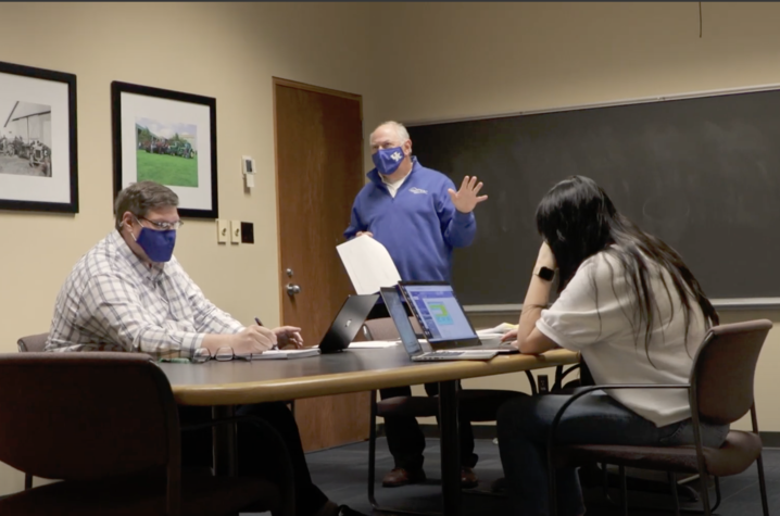 Wayne Sanderson in background of classroom with two students