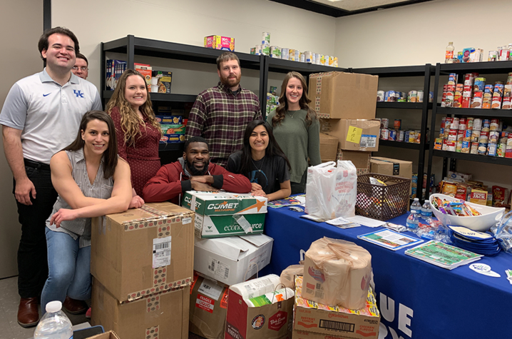 Students standing with donations at the Big Blue Pantry.