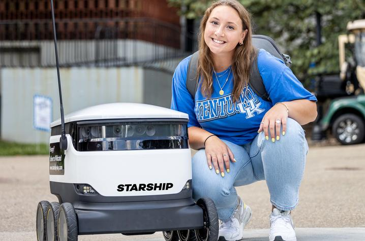 photo of student next to Starship robot