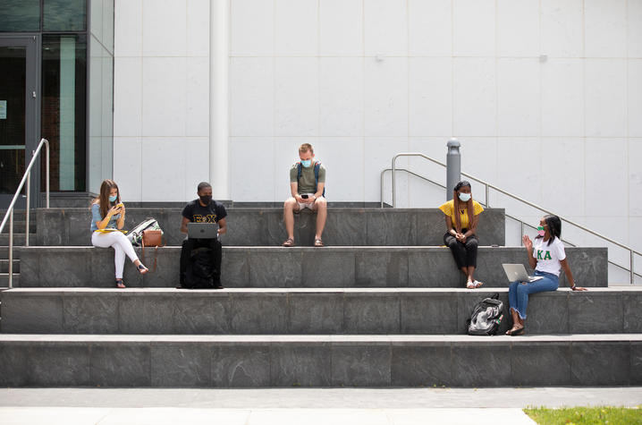 students with masks to protect from COVID-19 sitting on steps