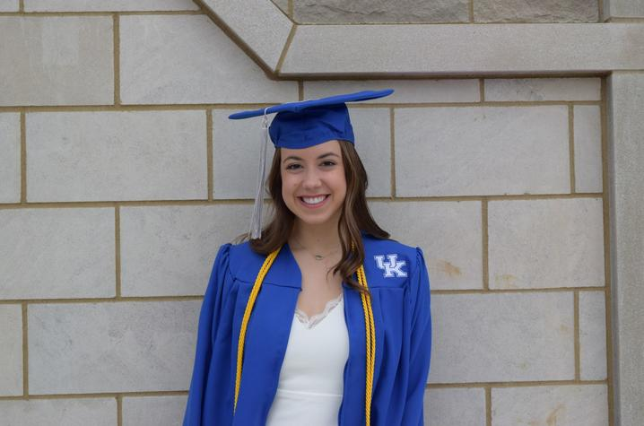 headshot photo of Sydney Sims in cap and gown outside Student Center