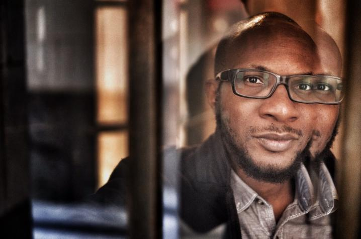photo of Teju Cole through window panes