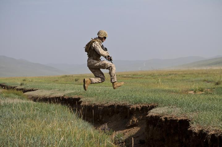U.S. Marine Lance Cpl. Nicholas Moore  jumps over a ditch during a cordon and search lane. Photo By Cpl. Robert Bush