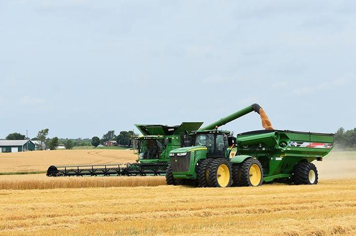 Hodgenville farmer Ryan Bivens empties wheat from his combine into a wagon driven by his son Cyrus. Bivens said he has seen outstanding crop yields the past 10 years. Photo by Katie Pratt, UK agricultural communications.
