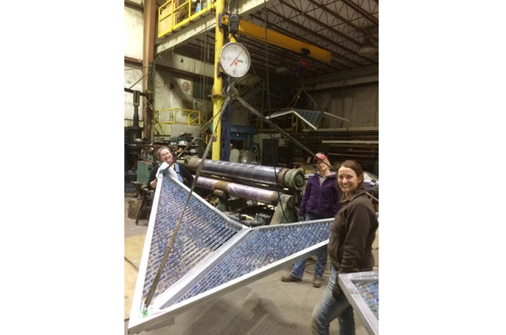 Photo of fabrication team with large blue kite