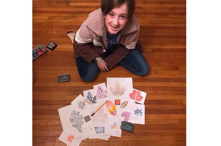 Brenna Mefford shows off her leaf print collection that she made in another 4-H program. 4-H'ers who become Junior Master Naturalists will make a similar collection