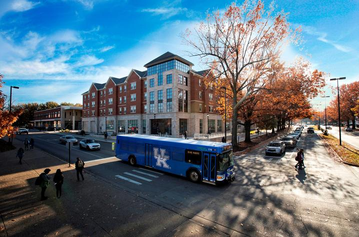 photo of bus passing by residence hall with fall trees