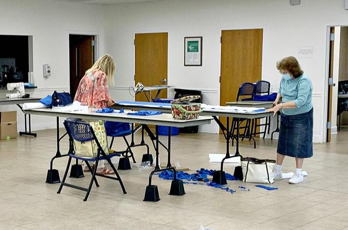 Extension Master Clothing Volunteers Ruby Hord, left, and Leoma Rigdon cut fabric to make surgical gowns that are used by regional health care workers administering COVID-19 tests.