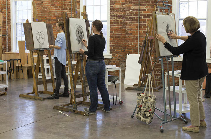 photo of 3 students drawing at easels in Fine Arts Institute class