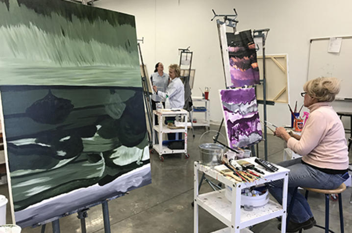 photo of woman painting at canvas between another 2 other canvas, other students in background