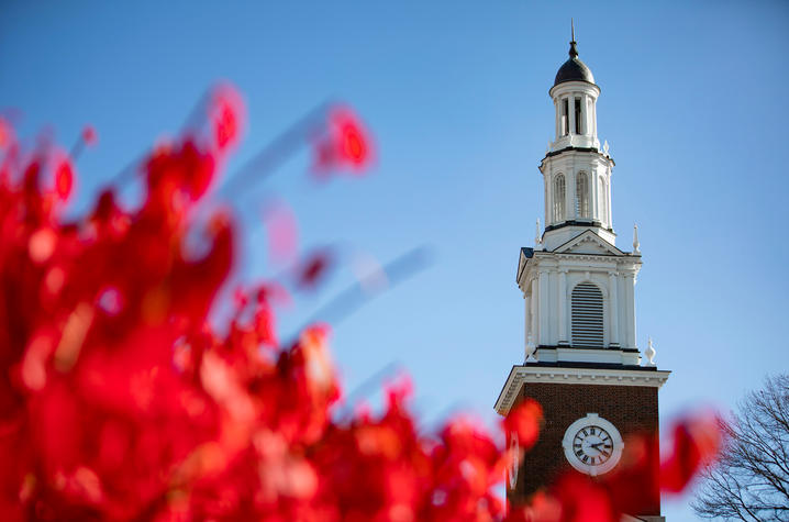 photo of Memorial Hall spire with bright red fall leaves in the foreground