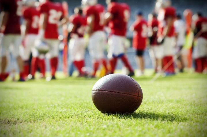 photo of football on field, team in background