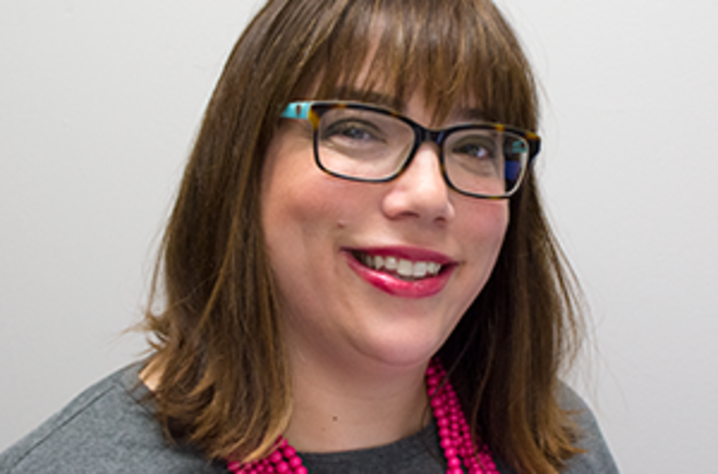 Headshot of Heather M. Bush, Ph.D.. She's in front of a white wall and wears a gray shirt, a multi-stranded necklace of pink peral-shaped beads, black glasses, and red lipstick. She medium-brown hair down to her should and hangs. She's smiling at the came