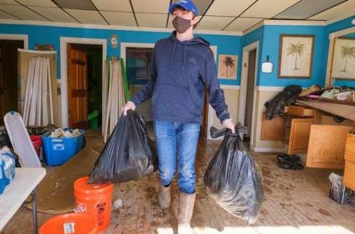 Ty Cheatham, AGR Fraternity member and a freshman agricultural and medical biotechnology major from Adair County, removes trash from a building in downtown Beattyville on March 5.