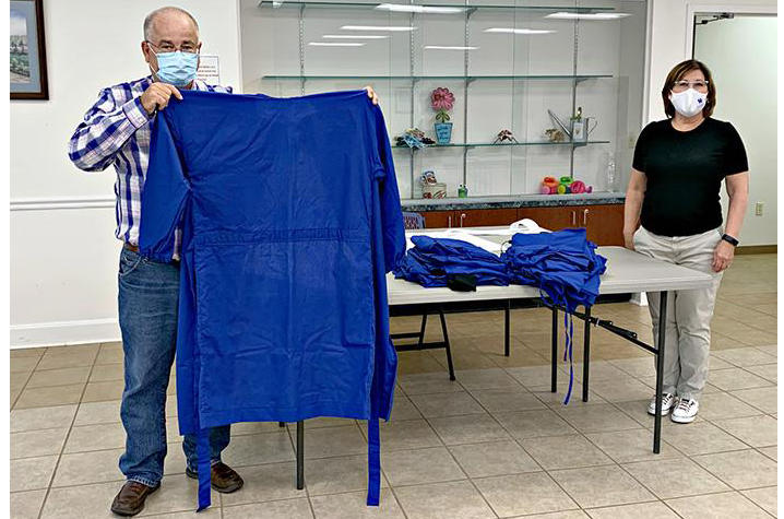 Steve Arnold (left) and Sherrill Bentley (right) show gowns completed by extension volunteers.