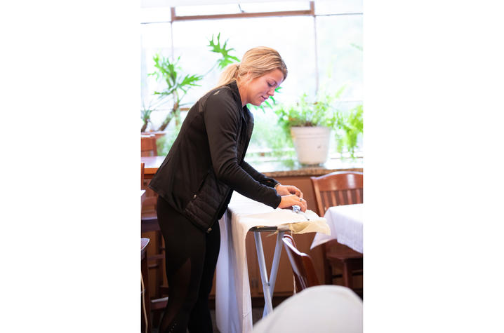 Student ironing a tablecloth for the Lemon Tree