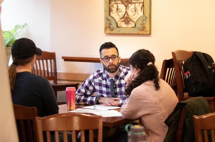 Aaron Schwartz seated at table speaking to two students