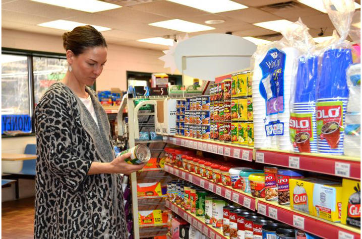Woman examines the label on a canned good in the grocery store