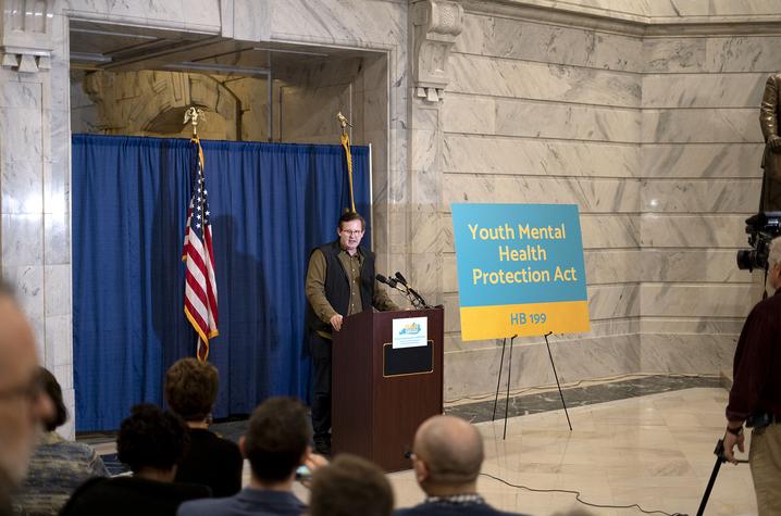 Michael Frazier speaking at podium