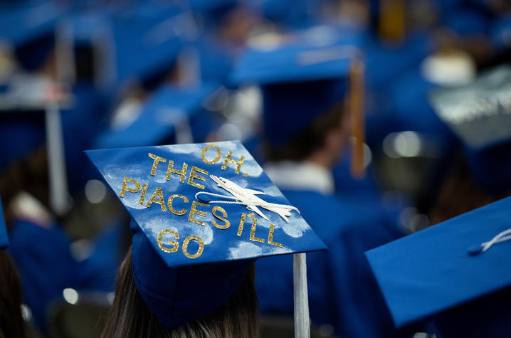 """grad wearing mortarboard with writing on it that says """"Oh, the places I'll go"""""""