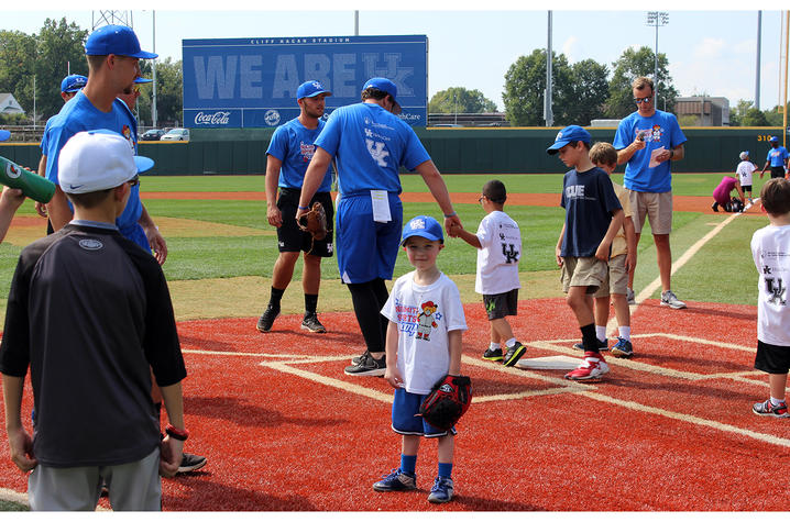Jaxon Russell, wearing a white t-shirt and blue UK baseball hat, stands with his back facing the baseball field.