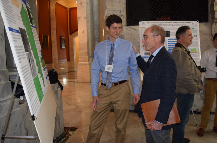 UK senior Adam Nolte explains his research on sinkholes in Woodford County to President Capilouto