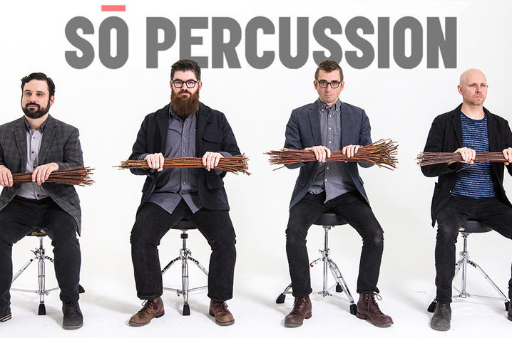 photo of Sō Percussion seated holding twigs with the band name behind them