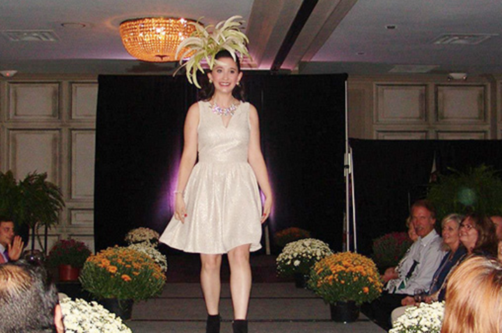 A girl in a gold dress walks down a runway.