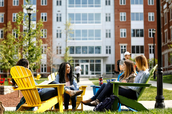 photo of students sitting in Adirondack chairs on campus