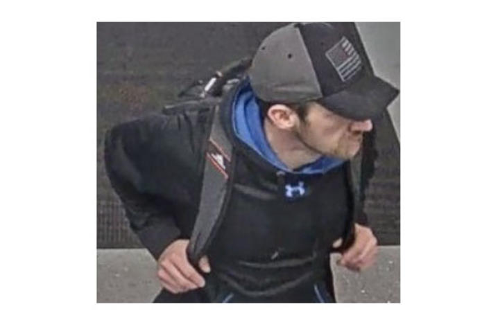 photo of suspect - white man in cap with backpack