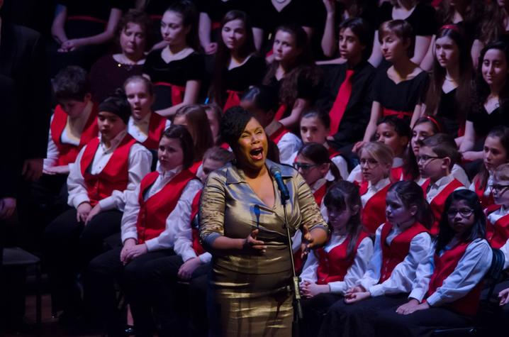photo of Angelique Clay singing solo in front of Lexington Singers Chidren's Choir a Collage
