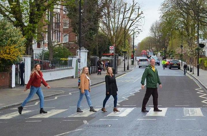 UK students from left: Catie Archambeau, Arizzona Albright and Emma Rosenzweig and Jason Swanson, UK associate professor, recreate the famous Beatles album cover at the Zebra Crossing at Abbey Road Studios in London
